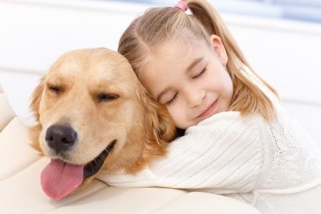 Girl hugging golden retriever