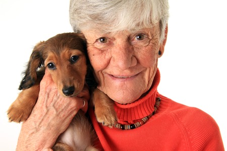 Senior woman holding small dog